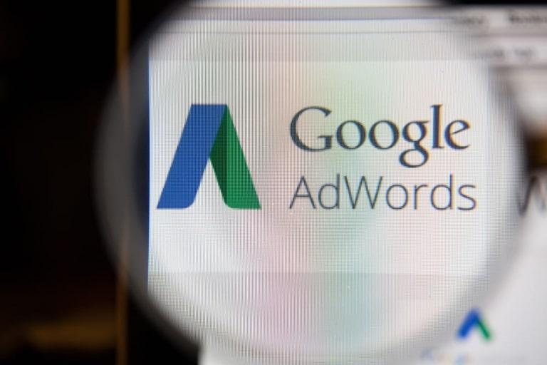 Coverbild zeigt eine Lupe, die auf in einem Browser geöfnette Adwords Oberfläche zeigt