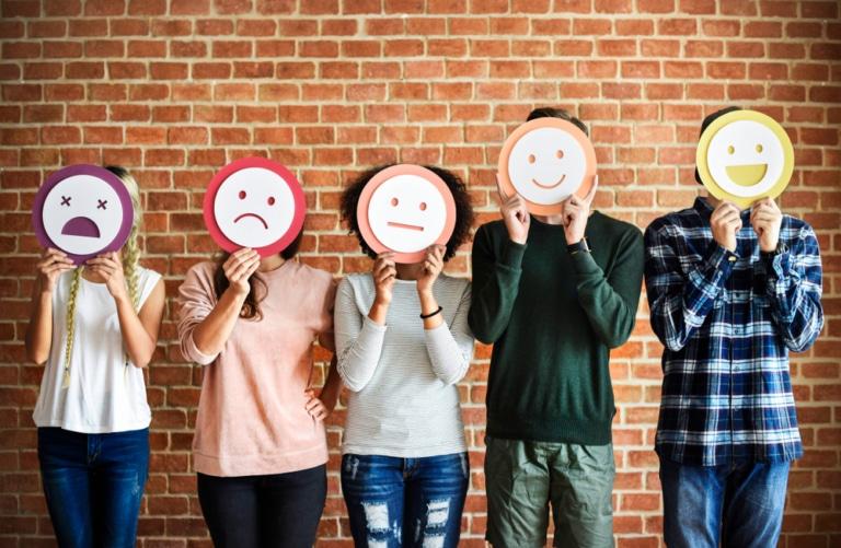 5 Menschen mit unterschiedlich emotionalen Smileys vor dem Gesicht