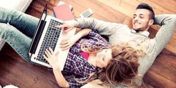 paar mit laptop auf dem boden