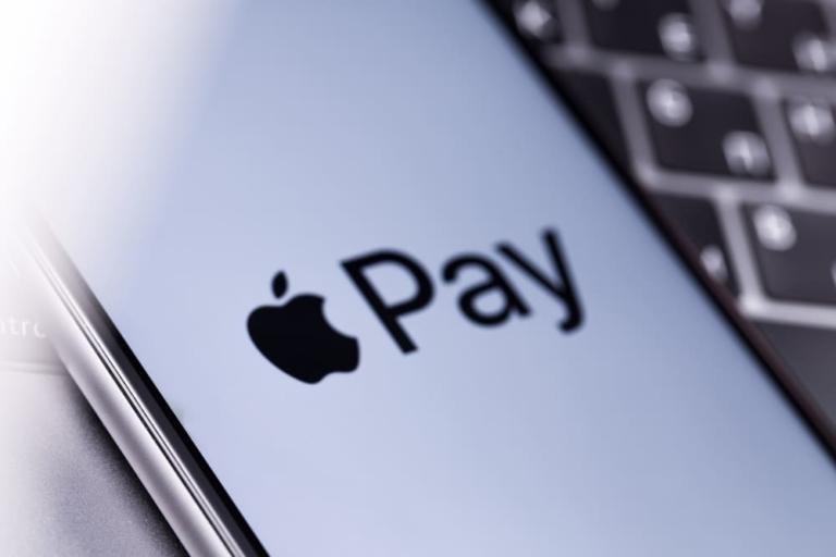 Zu sehen ist ein Apple iPhone mit Apple Pay Logo auf dem Display auf einer Tastatur.