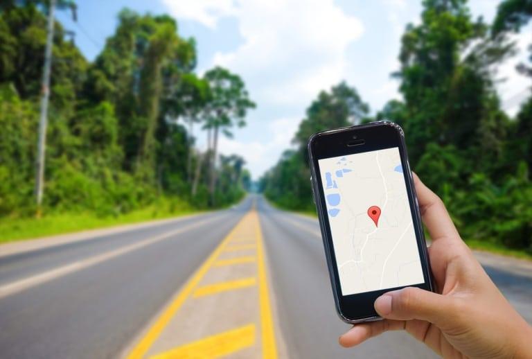 Eine im iPhone geöfnette Maps App vor Hintergrund einer endlosen Starße irgendwo im Outback
