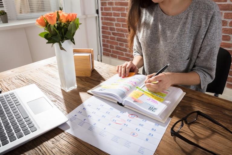 Frau mit Kalender am Tisch, Terminplanung