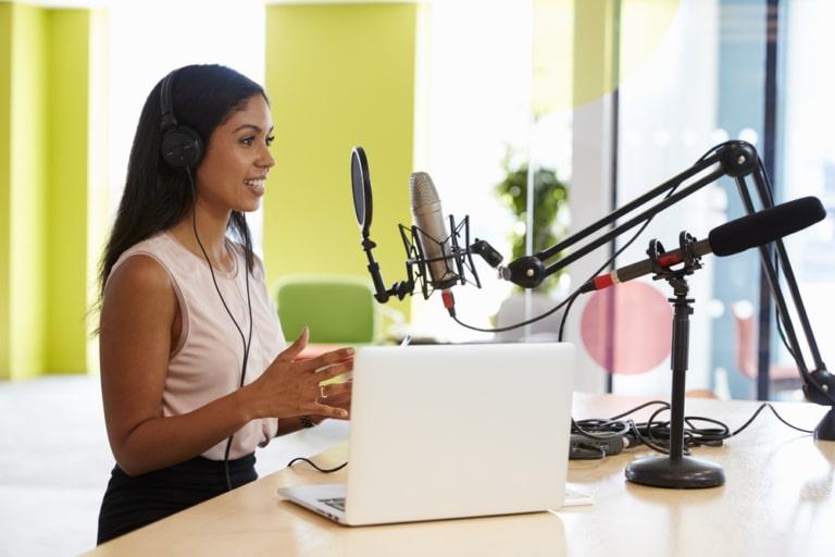 Frau nimmt einen Podcast im Studio auf