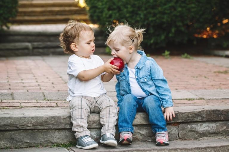 2 Kinder teilen sich ein Apfel
