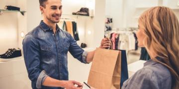 Mann übergibt Einkaufstasche einer jungen Dame