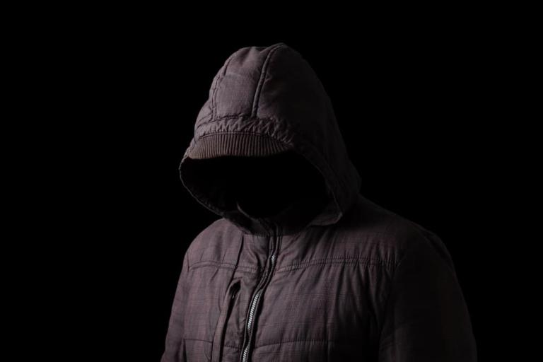 Mann versteckt sich im Dunkeln unter einer schwarzen Kapuze