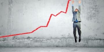 Mann springt nach oben und freut sich wegen der Umsatzsteigerung