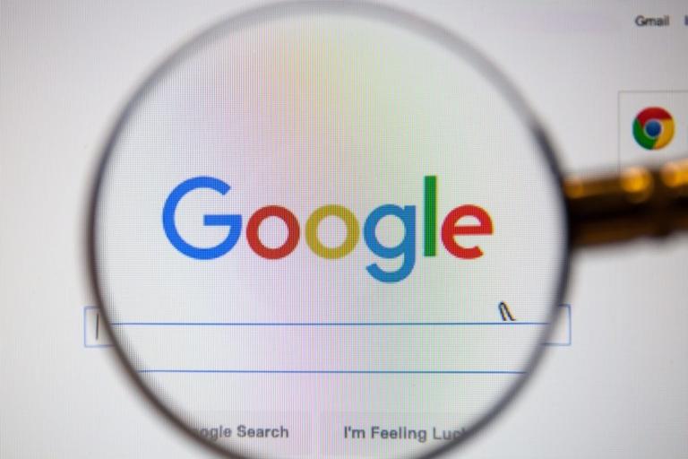 Eine Lupe die über der Google Startseite gehalten wird.