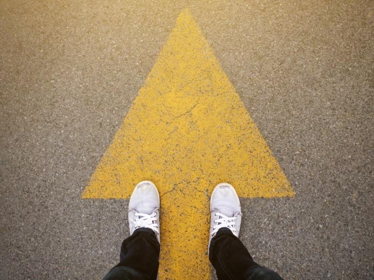 Ein Jemand steht über einem auf Asphalt gemalten gelben Pfeil,