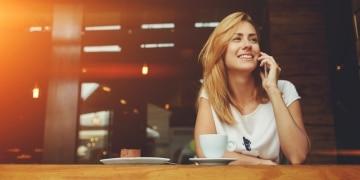 EIne junge Frau telefoniert im Cafe