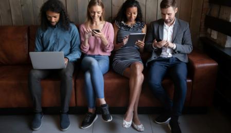 Verschiedene junge Menschen, die elektronische Geräte benutzen