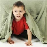 Junge schaut unter Decke hervor